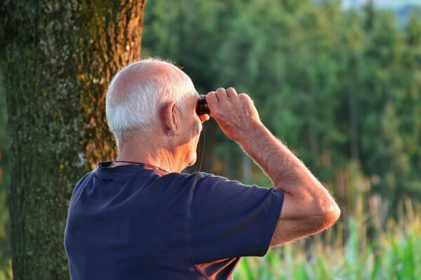An image of a retired man using binoculars to trace his pension