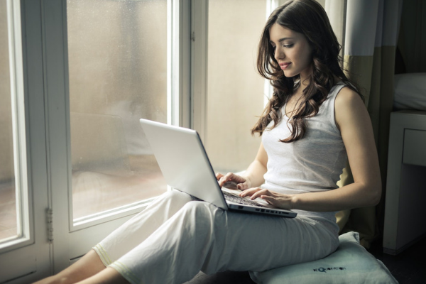 A picture of a female freelancer working on her laptop sitting by a window at home